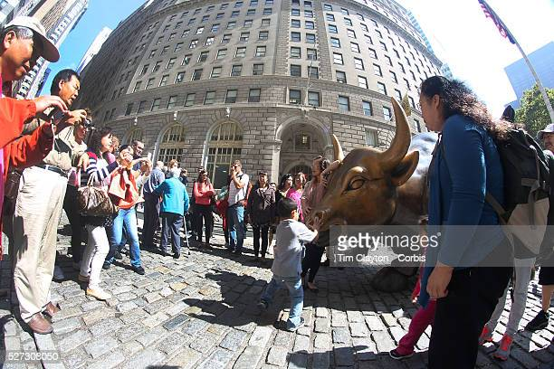 Tourists take pictures with The Charging Bull Monument and Landmark Outdoor Sculpture and Public Art Bowling Green New York City USA 16th September...