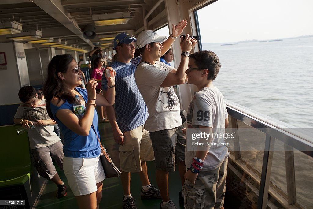 Tourists take pictures with the Statue of Liberty in the background June 20, 2012 while riding the Staten Island Ferry in New York City.