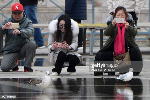 Tourists take pictures with their mobile phones at Piazza San Marco on January 19 2018 in Venice / AFP PHOTO / Andrea PATTARO