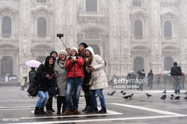 Tourists take 'selfies' as snow falls in Duomo Square in Milan on March 2 2018 Fresh heavy snowfalls and icy blizzards are lashing Europe as the...