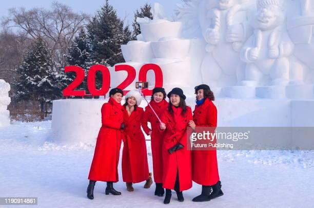 HARBIN CHINA DECEMBER 27 2019 Tourists take selfies at Harbin Sun Island International Snow Sculpture Art Expo Harbin Heilongjiang Province China...