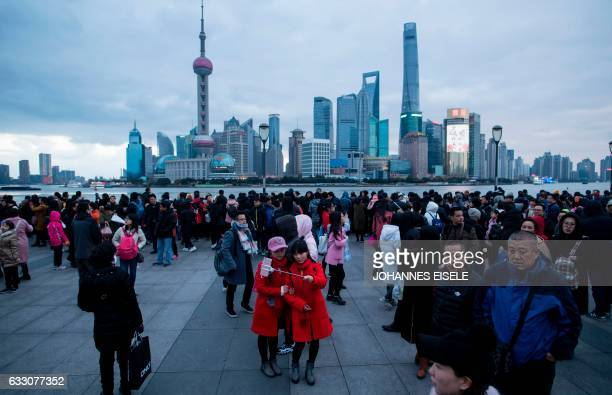 TOPSHOT Tourists take selfies at the bund overlooking the financial district of Lujiazui of Shanghai during the Spring Festival holidays on January...