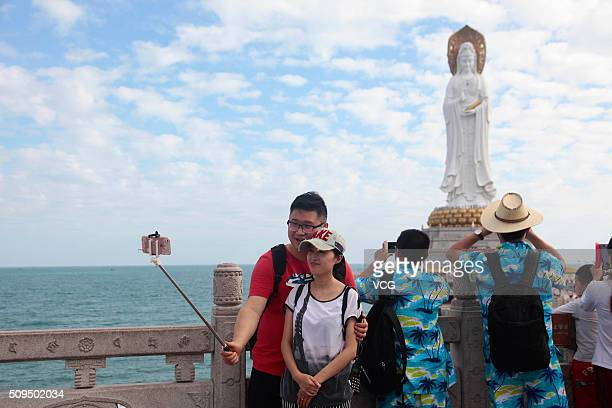 Tourists take selfies with the Guan Yin of the South Sea during the Spring Festival holiday on February 10 2016 in Sanya Hainan Province of China The...