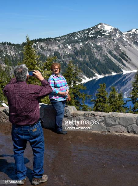 Tourists take souvenir photographs from a scenic overlook on the rim of Crater Lake in Oregon The lake a waterfilled caldera of an ancient volcano...