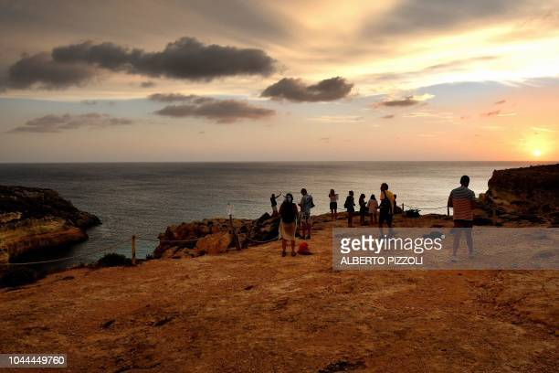 Tourists take sunset photos in front of the Isola dei Conigli in Lampedusa on September 25 2018 Five years after the worst shipwreck of its history...
