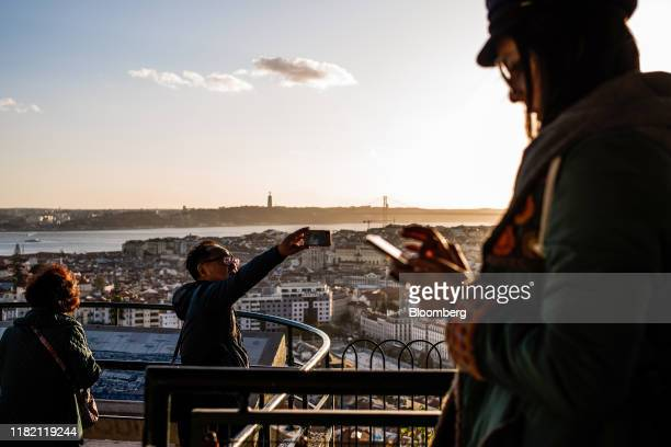A tourists takes a smartphone photograph of the view from Miradouro da Senhora do Monte in Lisbon Portugal on Friday Nov 8 2019 While Spain's debt...