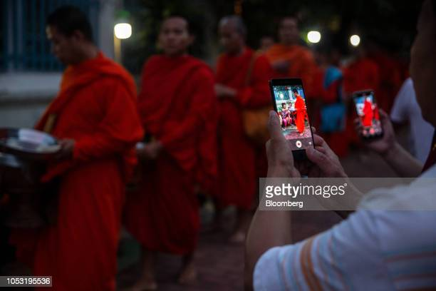 Tourists takes photographs as monks collect alms at a ceremony in Luang Prabang Laos on Monday Oct 22 2018 Laos's economy is set to expand at 7...