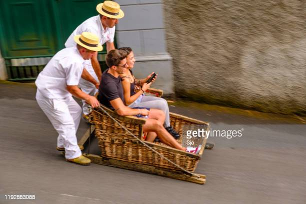 tourists taking a ride in a tradional wicker toboggan down the hill from monte in funchal on madeira island in portugal - straw boater hat stock pictures, royalty-free photos & images