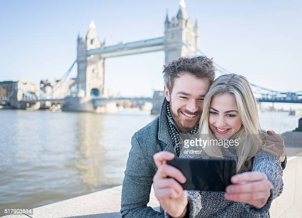 tourists taking a selfie in london with tower bridge - ロンドン サウスバンク ストックフォトと画像
