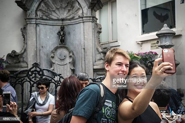 Tourists taking a selfie with the Manneken Pis in Brussels.
