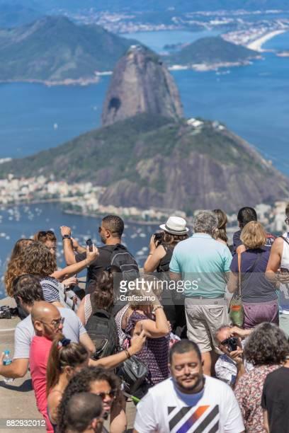 turistas tirando foto do pão de açúcar e da baía de guanabara no rio de janeiro brasil em um dia quente de verão - pão de açúcar - fotografias e filmes do acervo