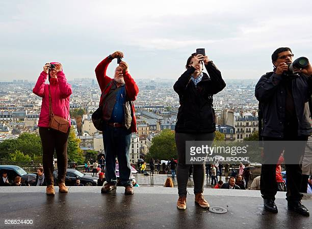 Tourists taking photographs of the Basilica of Sacre Coeur and selfies in Montmartre A view of Paris is seen below them Montmartre is a hill in the...
