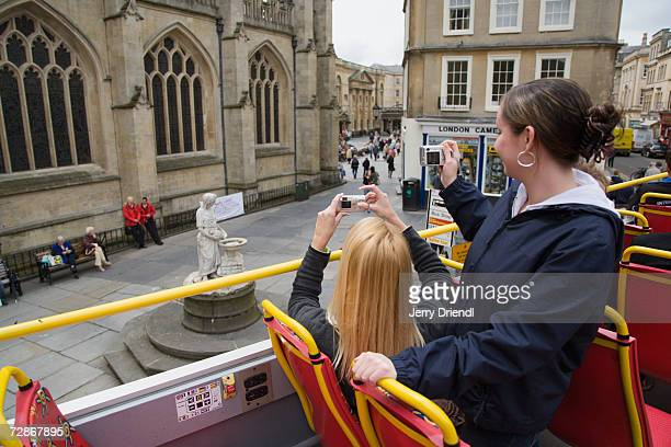 Tourists taking photographs on open top bus