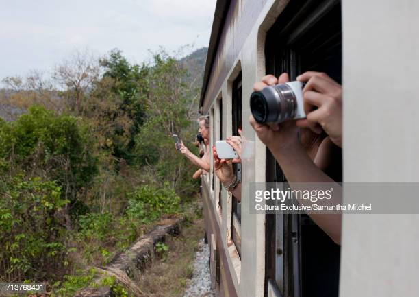 Tourists taking photographs out of train window, Burma railway aka Death Train, near Kanchanaburi, Thailand