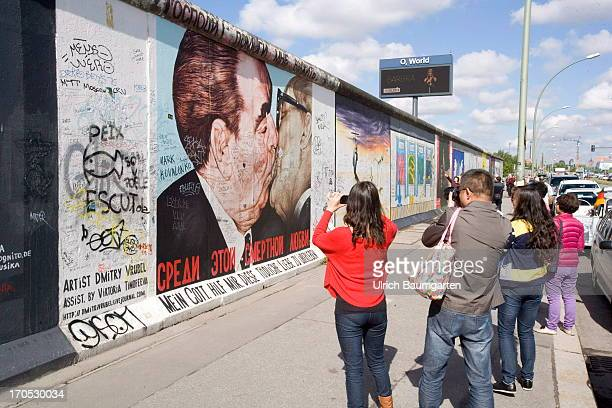 Tourists taking photos at the EastSideGallery in Berlin an open air gallery on an old piece of the Berlin Wall on May 27 2013 in Berlin Germany