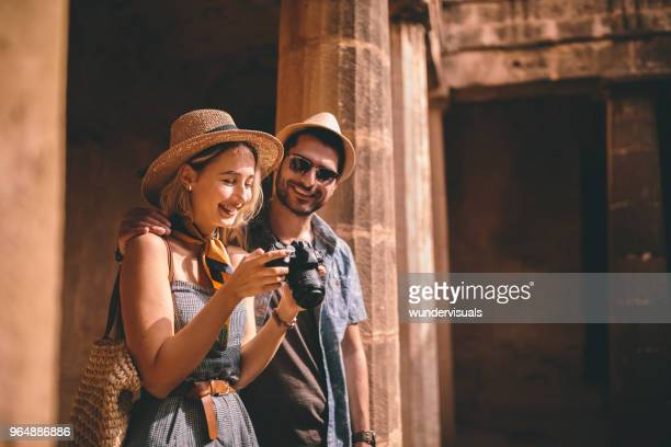 Tourists taking photos of ancient Italian monument with stone columns
