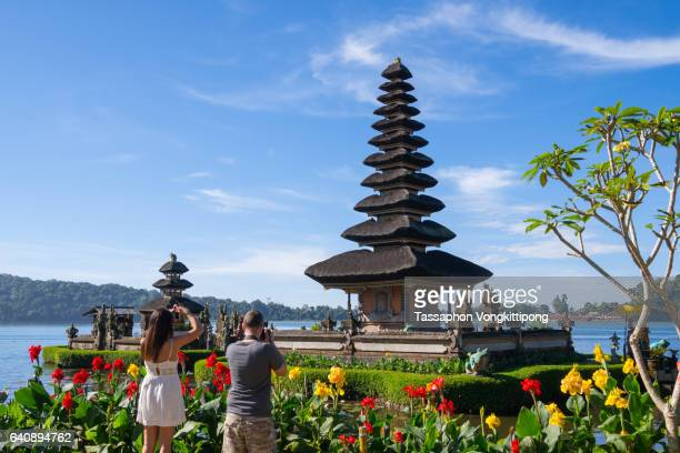 tourists taking photos of beratan temple pagoda in bali, indonesia - tanah lot stock pictures, royalty-free photos & images