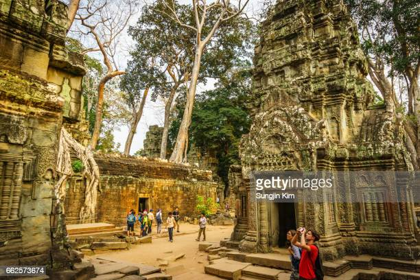 Tourists taking picture at old ruin of Ta Prohm Temple at Siem Reap