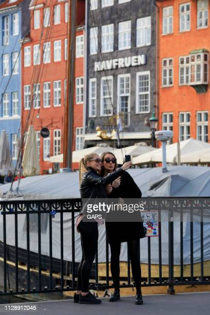 tourists taking pictures and selfies at nyhavn in copenhagen - nyhavn stock pictures, royalty-free photos & images
