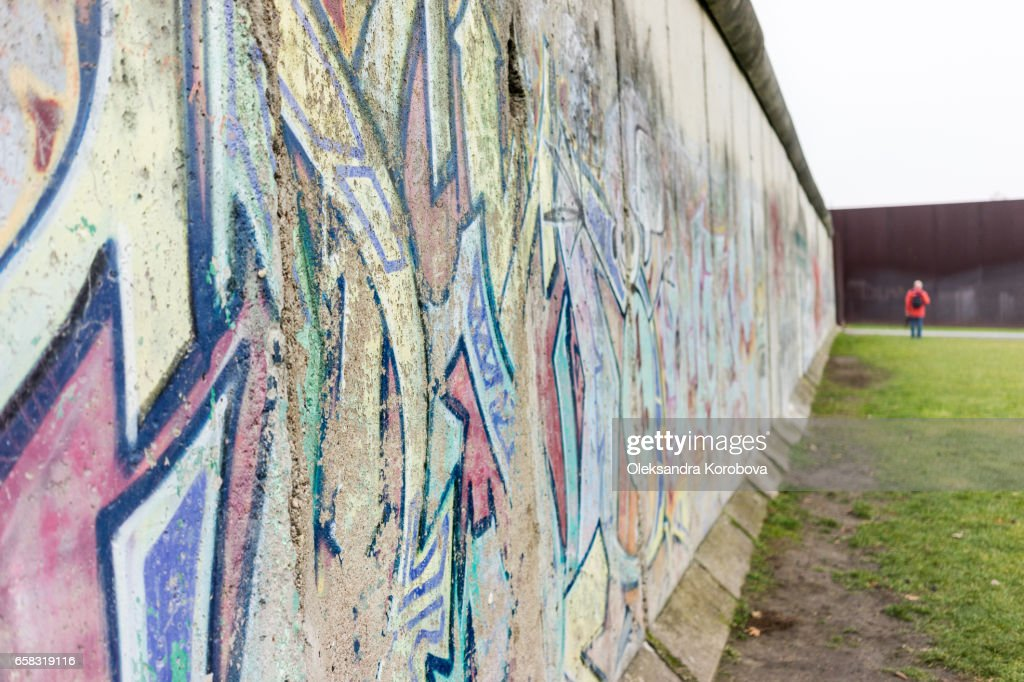 Berlin, Germany - December 20, 2016. Tourists taking pictures at the Berlin Wall memorial in Germany. Writing is visible on the cement wall. Two sides of the wall - East and West Berlin. : Stock Photo