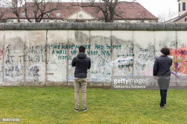 berlin, germany - december 20, 2016. tourists taking pictures at the berlin wall memorial in germany. writing is visible on the cement wall. two sides of the wall - east and west berlin. - istock stock pictures, royalty-free photos & images