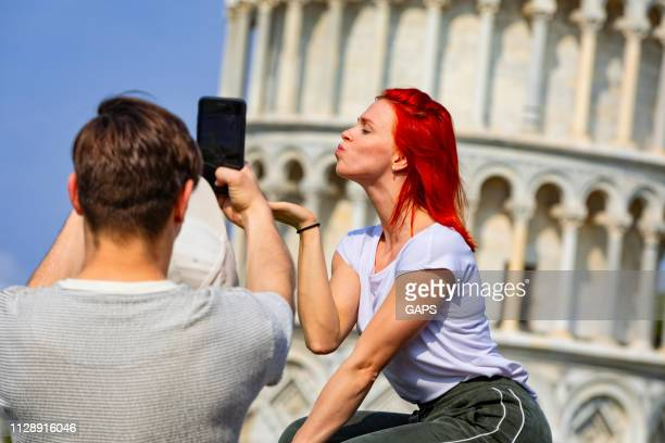 tourists taking pictures of themselves in front of the famous leaning tower of pisa - asymmetry stock pictures, royalty-free photos & images