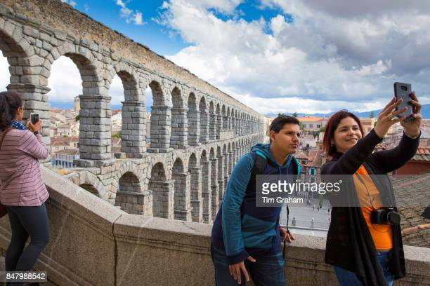 Tourists taking selfie photographs with smartphone at famous spectacular Roman aqueduct Segovia Spain