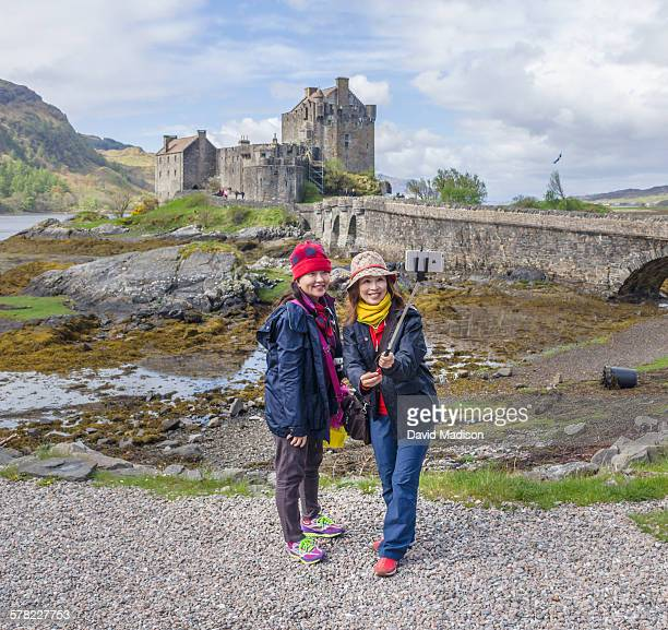 Tourists taking selfie with Eilean Donan Castle.