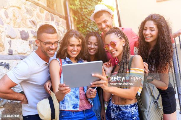 Tourists taking selfie with tablet on street