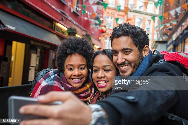 tourists taking selfies on vacation in dublin ireland - irish flag stock pictures, royalty-free photos & images