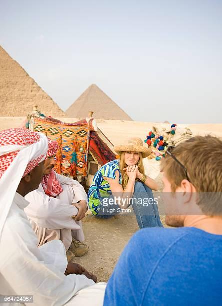 tourists talking with egyptians in front of pyramids - hugh sitton stock-fotos und bilder