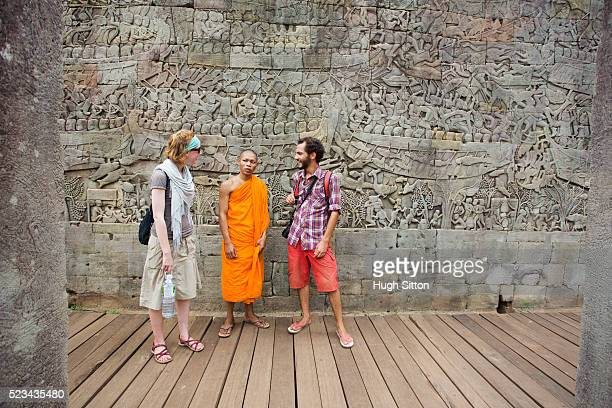 tourists talking with local monk, angkor wat, cambodia - hugh sitton bildbanksfoton och bilder
