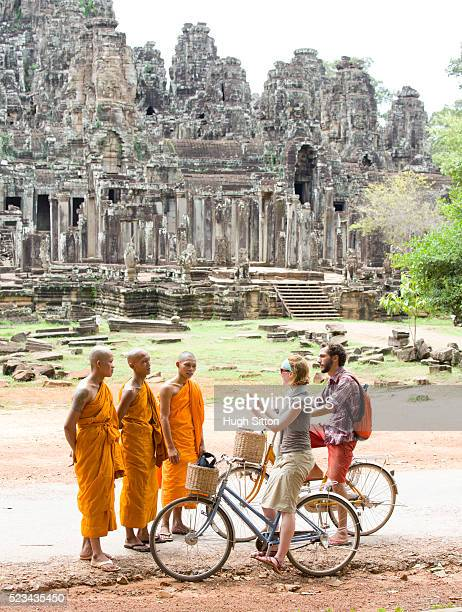 tourists talking with local monks, angkor wat, cambodia - hugh sitton stock pictures, royalty-free photos & images