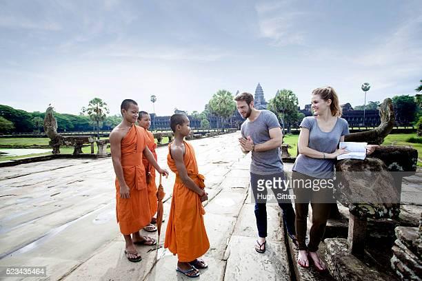 tourists talking with local monks, angkor wat, cambodia - hugh sitton bildbanksfoton och bilder