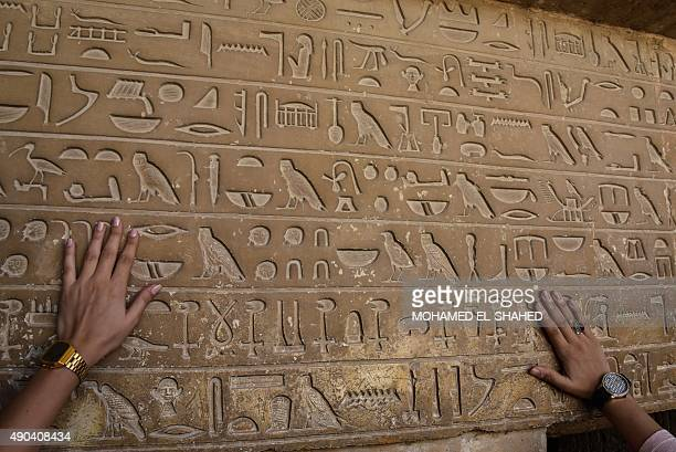 Tourists touch ancient hieroglyphics as they visit the Giza pyramids on the southern outskirts of the Egyptian capital Cairo on September 27 2015 AFP...