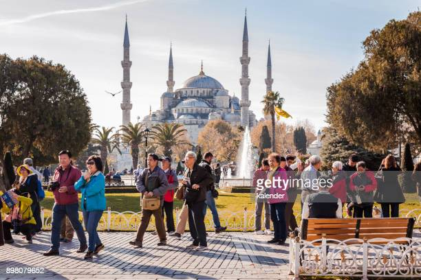 tourists travel in front of blue mosque in istanbul, turkey - istanbul province stock pictures, royalty-free photos & images