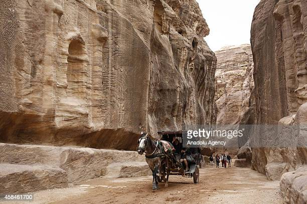 Tourists travel with carriage through The Siq the main entrance to historical Petra city of southern Jordanian governorate Ma'an on October 20 2014...