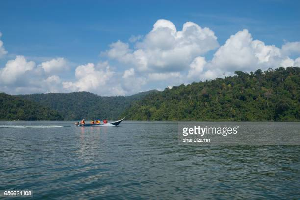tourists travelling by boat  at temengor lake at royal belum rainforest in perak malaysia.royal belum is one of the top rain forest attraction in the country. - shaifulzamri stock pictures, royalty-free photos & images