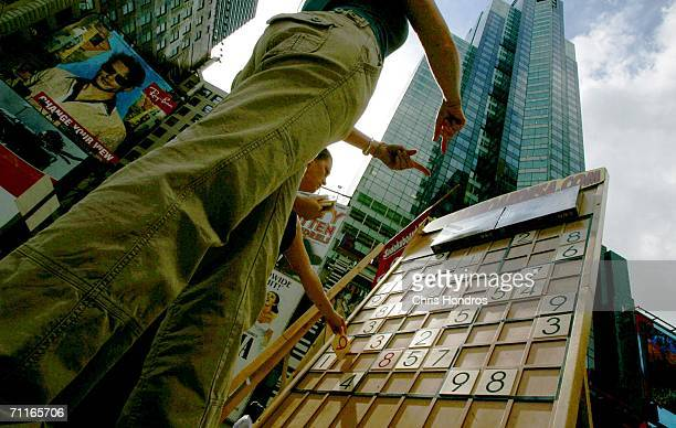 Tourists try to complete a giant Sudoku puzzle June 9 2006 in Times Square in New York A game company set up a large board featuring the popular...