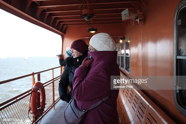 Tourists try to stay warm on the Staten Island Ferry as it leaves Manhattan on February 19, 2015 in New York City. New York, and much of the East...