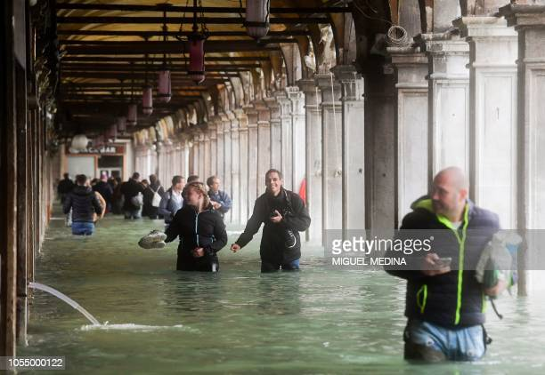 Tourists under arches next to the flooded St Mark's Square during a highwater alert in Venice on October 29 2018 The flooding caused by a convergence...