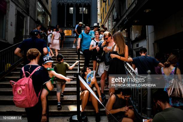 Tourists use fans as they queue to get on Santa Justa lift in downtown Lisbon on August 3 2018 Two men died from heatstroke in Spain as Europe...