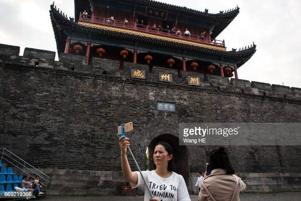 Tourists use iPhone take pictures in Ancient City on April 152017 in jingzhouHubei provinceChinaJingzhou with a history of more than 2600 years is...