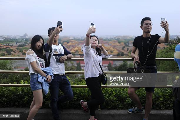 Tourists use mobile phones to take selfies at a park near the Forbidden City in Beijing on May 4 2016 / AFP / WANG ZHAO