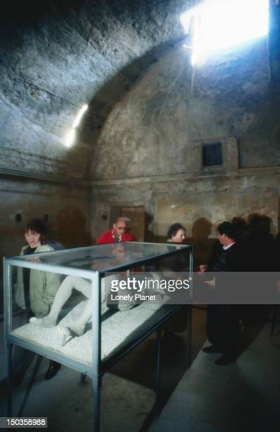 Tourists view a fossilised body - Pompeii, Campania