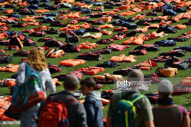 Tourists view lifejackets that have been used by refugees to cross the sea to Europe as they are laid out in Parliament Square on September 19 2016...