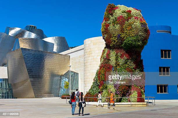 Tourists view Puppy flower feature floral art by Jeff Koons at Guggenheim Museum in Bilbao Basque Country Spain