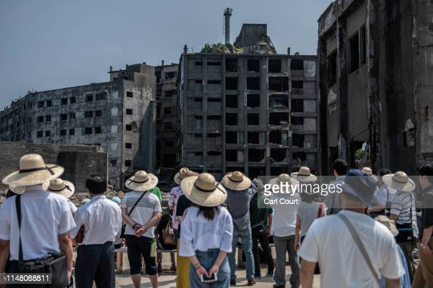 Tourists view ruined buildings during a visit to Hashima Island on June 5, 2019 near Nagasaki, Japan. Now a popular tourist destination, Hashima...