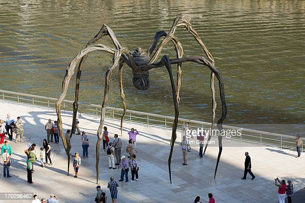 Tourists view spider bronze sculpture Maman by Louise Bourgeois at Guggenheim Museum in Bilbao, Basque country, Spain