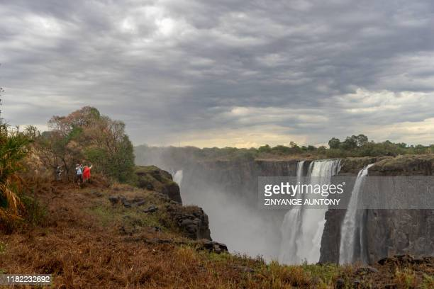 Tourists view the majestic Victoria Falls a major tourism attraction for Zimbabwe Victoria Falls on November 13 2019 A series of heat waves has dried...